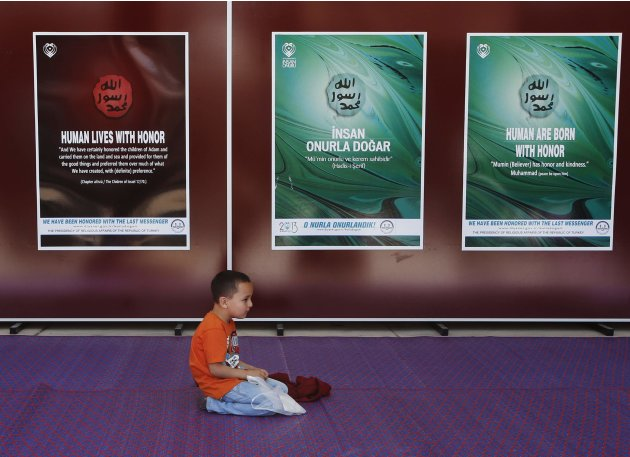 A boy sits in front of posters at the Ottoman-era Sultanahmet mosque, also known as the Blue Mosque, in Istanbul
