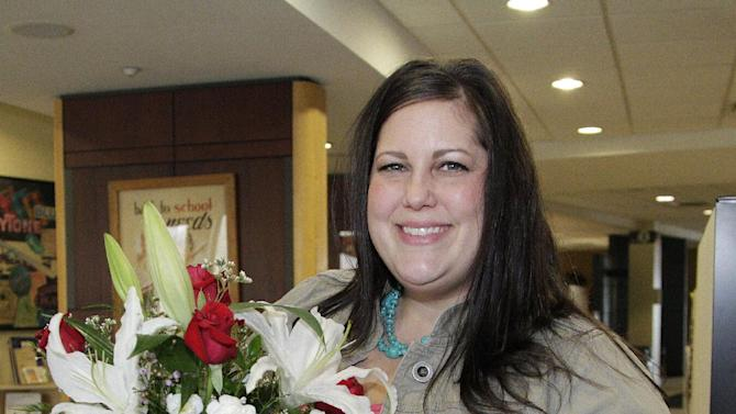 """IMAGE DISTRIBUTED FOR TELEFLORA- Amber Cardarella shows off her Heartstrings Bouquet and beautiful $15,000 diamond necklace that her husband Matt won for her in Teleflora's """"Love Rocks"""" sweepstakes, Thursday, Feb. 14, 2013, in Dayton, Ohio. (Jay LaPrete/AP Images for Teleflora)"""