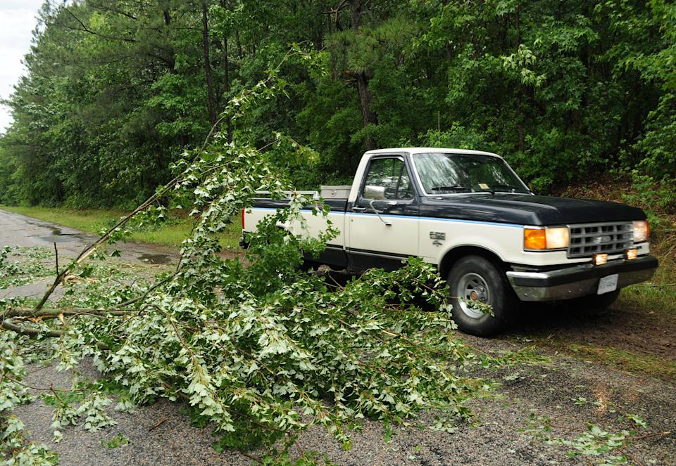A truck drives off-road to avoid a tree downed on a frontage road next to Interstate 95 in Prince George County, Va. as a severe storm brought down trees and power lines across the area, Thursday, June 13, 2013. (AP Photo/The Progress-Index, Patrick Kane)