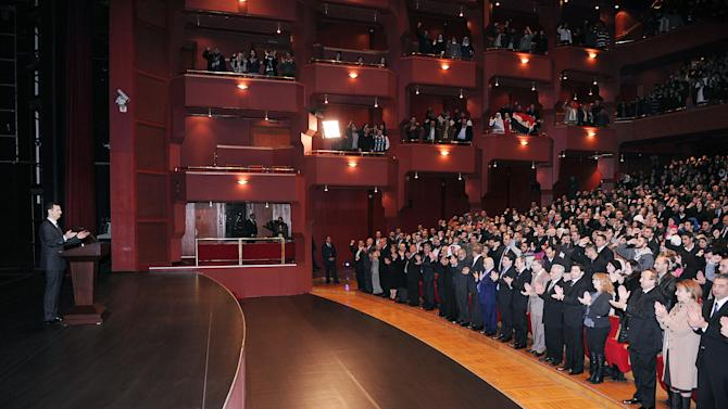 In this photo released by the Syrian official news agency SANA, Syrian President Bashar Assad, left, greets his supporters as he speaks at the Opera House in central Damascus, Syria, Sunday, Jan. 6, 2013. Syrian President Bashar Assad on Sunday outlined a new peace initiative that includes a national reconciliation conference and a new government and constitution but demanded regional and Western countries stop funding and arming rebels first. (AP Photo/SANA)