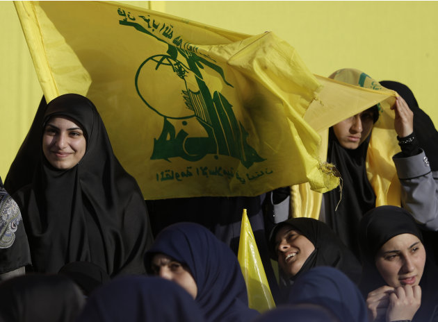 "Hezbollah supporters hold Hezbollah flags as they listen to the broadcast of a speech by Hezbollah leader Sheik Hassan Nasrallah, during a rally commemorating ""Liberation Day,"" which marks the withdra"