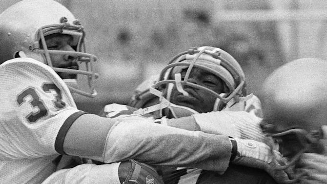 In this Jan. 1, 1979, file photo, Eric Herring, University of Houston flanker, is grabbed around the neck by Jim Browner (33) Notre Dame safety, and another Notre Dame player after Herring took a pass from quarterback Danny Davis in the second quarter of the Cotton Bowl game in Dallas. Ailing quarterback Joe Montana led the Fighting Irish to a come-from-behind victory on a frigid day in Dallas. The Irish scored 23 points in the fourth quarter