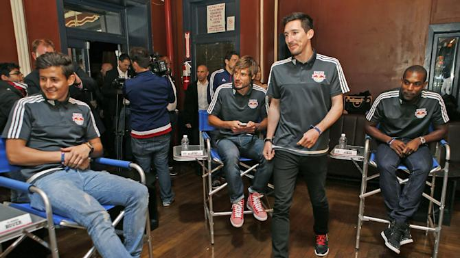 New York Red Bulls forward Sacha Kljestan, third from right, heads to his seat at the start of the Major League Soccer club's media day in New York, Tuesday, March 3, 2015.  From left, midfielder Ruben Bover, of Spain, defenders Damien Perinelle, of France, and Ronald Zubar of Guadeloupe look on. (AP Photo/Kathy Willens)