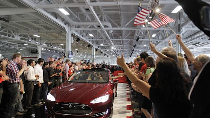 FILE - In this June 22, 2012 file photo, Tesla workers cheer on the first Tesla Model S cars sold during a rally at the Tesla factory in Fremont, Calif.  The Tesla Motors Inc. Model S electric car has tied an older Lexus for the highest score ever recorded in Consumer Reports magazine's automotive testing on Thursday, May 9, 2013. (AP Photo/Paul Sakuma, File)