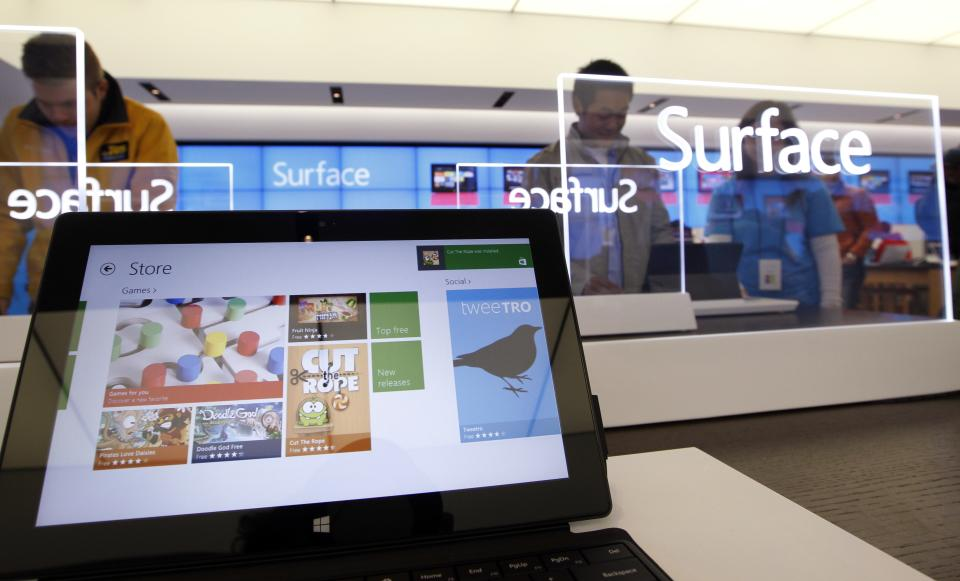 Customers look over new Microsoft Surface tablet computers Friday, Oct. 26, 2012, at a Microsoft store in Seattle. Friday was the first day of sales for the new Windows 8 operating system and the company's new tablet computer, the Surface. (AP Photo/Elaine Thompson)