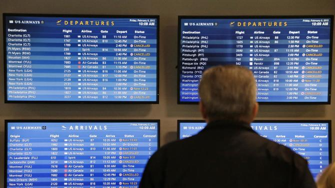 TV monitors at Logan International Airport in Boston show cancelled flights Friday morning, Feb. 8, 2013.  Boston and much of eastern Massachusetts was under a blizzard warning until 1 p.m. Saturday. Logan International Airport said it would try to stay open during the storm but airlines had already canceled many flights through Saturday. (AP Photo/Gene J. Puskar)