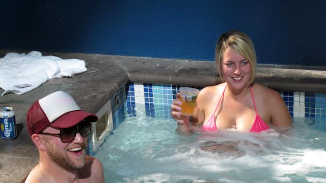 FILE - In this Oct. 16, 2012, file photo, Evan Wajda, left, and Melissa Punska, both of Rye, N.H., sit in a jacuzzi at Harrah's in Atlantic City, N.J. Atlantic City's efforts to diversify itself and become less dependent on gambling appear to be paying off after nearly a decade. (AP Photo/Wayne Parry, File)