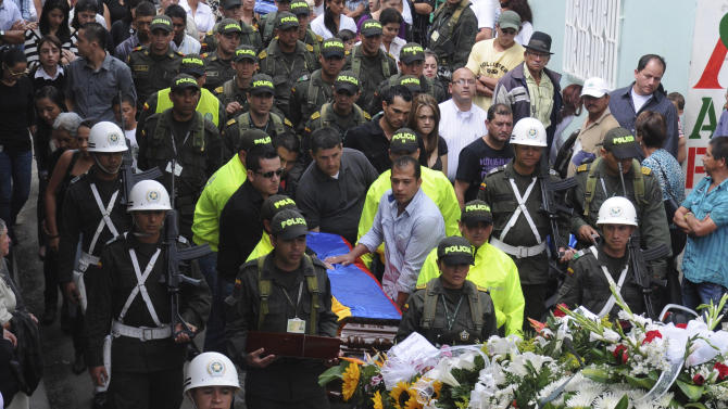 Relatives and fellow police officers carry the coffin containing the body of police officer Andres Rodriguez during his funeral service in Guarne, Colombia, Monday, April, 30, 2012. Colombia's Defense Minister Juan Carlos Pinzon said his government has not launched any special rescue mission for Romeo Langlois, a French journalist who was accompanying a counterdrug mission when it was attacked by leftist rebels on Saturday, killing Rodriguez. (AP Photo/Luis Benavides)