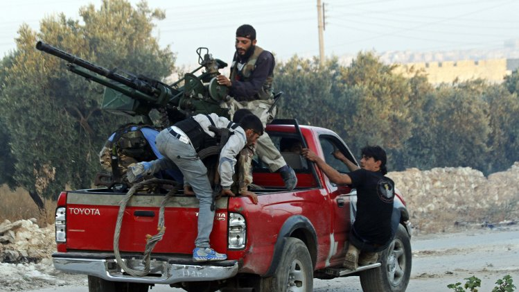 Free Syrian Army fighters man an anti-aircraft gun on a truck in the village of Aziza, in the southern countryside of Aleppo