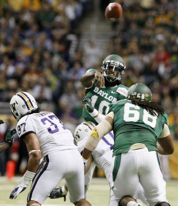 Baylor quarterback Robert Griffin III, rear, throws a pass during the first half of the Alamo Bowl college football game against Washington, Thursday, Dec. 29, 2011, at the Alamodome in San Antonio. (