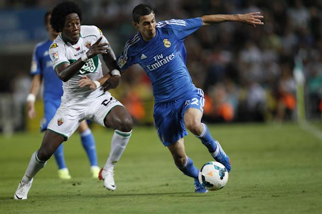 Real Madrid's Angel Di Maria from Argentina, right, duels for the ball with Elche's  Carlos Alberto Sanchez Moreno, left,  during their La Liga soccer match at the Martinez Valero stadium in Elche, Sp