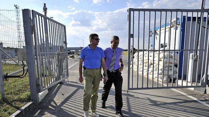 The head of the OSCE (Organization for Security and Cooperation in Europe) mission, acting Chief Observer Paul Picard, right, walks with Vadim Artyomov, deputy governor of Rostov region, left, while visiting the Gukovo border checkpoint at Russia-Ukraine border in a small town of Gukovo, 120 kms (75 miles ) from Rostov-on-Don, Russia, Wednesday, July 30, 2014. The mission will be based in the city of Kamensk-Shakhtinskiy, in the Rostov-on-Don region. (AP Photo/Sergei Pivovarov)