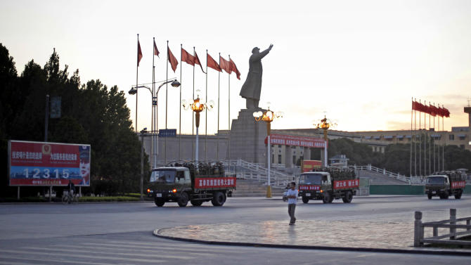 FILE - In this July 10, 2009 file photo, a military convoy passes a statue of late Chinese leader Mao Zedong in Kashgar, China. China on Monday, Aug. 1, 2011 blamed Muslim extremists trained in Pakistan for an attack that killed six civilians in one of the most troubled ethnic regions where police later fatally shot five suspects. (AP Photo/Elizabeth Dalziel, File)