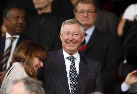 Manchester United's former manager Alex Ferguson smiles in the stands before their English Premier League soccer match against Queens Park Rangers at Old Trafford in Manchester