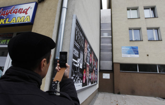 A man takes a picture of the one of the world's narrowest buildings, built as an artistic installation wedged between two existing buildings, in Warsaw