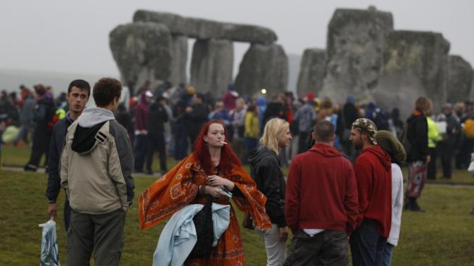 People gather during the summer solstice at Stonehenge, near Salisbury Thursday, June 21, 2012. Rain-sodden crowds welcomed a spectacularly rainy summer solstice at Stonehenge in true British fashion Thursday: With stoicism and wit. But through the wind and rain, drummers inside the ancient stone circle kept up their thumping rhythm, new age pagans kept up their chaotic dance, and visitors kept up their sense of humor. (AP Photo/Lefteris Pitarakis)