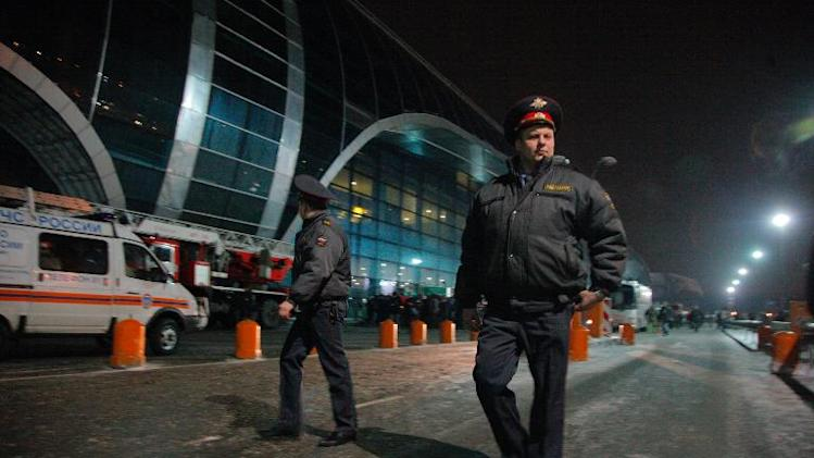 Police officers patrol outside Moscow's Domodedovo international airport on January 24, 2011, soon after an explosion