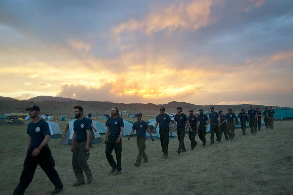 In a photo made on Tuesday, June 19, 2012, and made available on Wednesday by the Colorado National Guard, firefighters from the Monument, Colo., fire department march to dinner at sunset in a base camp near the High Park wildfire about 15 miles west of Fort Collins, Colo.(AP Photo/Colorado National Guard, John Rohrer)