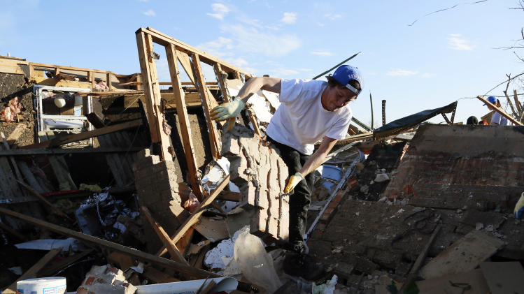 Josh Sallee throws a piece of a brick wall from a tornado-destroyed home on Heather Lane in Moore
