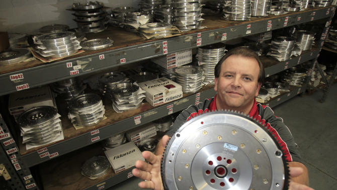 """In this Wednesday, Sept. 5, 2012 photo, Ed Burgy, vice president of sales and marketing for Fidanza, holds up a lightweight aluminum flywheel in Perry, Ohio. Burgy, a supporter of President Barack Obama, sees former Massachusetts Gov. Mitt Romney's plan to cut income tax rates across the board, including for the wealthiest households, as a return to trickle-down economics. """"I'm 46 and I've never seen it trickle down to me,"""" he says. """"The people who own the companies - they don't trickle it down to the employees. ... Show me the proof and I'll listen to you."""" (AP Photo/Tony Dejak)"""