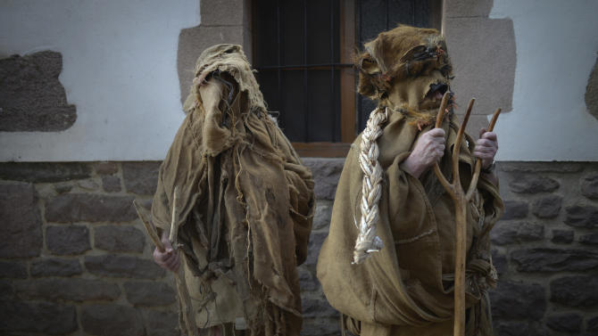 Villagers dressed in sacks and holding wooden rakes take part in carnival celebrations in the Navarran village of Lantz