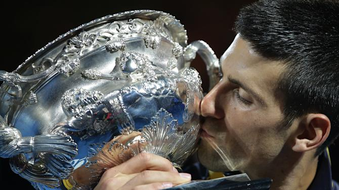 Serbia's Novak Djokovic kisses his trophy after defeating Britain's Andy Murray in the men's final at the Australian Open tennis championship in Melbourne, Australia, Monday, Jan. 28, 2013. (AP Photo/Dita Alangkara)