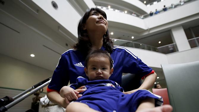 Japan's soccer fan Yui Okamoto and her fivemonth-old son Jun cheer for their team's FIFA Women's World Cup semi-final soccer match against England on a big screen during a public viewing event in Tokyo