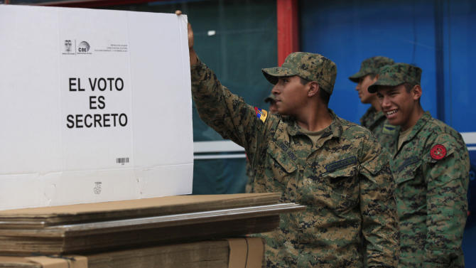 """Soldiers stand near ballot boxes, one that reads in Spanish """"The vote is secret,"""" as they are organized for upcoming elections for president and lawmakers, at the CEMEXPO, a warehouse used by the National Election Council in Quito, Ecuador, Friday, Feb. 15, 2013. Ecuador's elections will be held on Sunday. (AP Photo/Dolores Ochoa)"""
