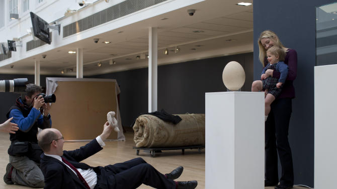 Alexander Robinson, aged 16 months, is held up by his mother Alexandra to be photographed next to a sub-fossilised pre-17th century Elephant Bird egg at the auction house's premises in London, Wednesday, March 27, 2013.  The Elephant Bird egg, which is estimated to fetch 20,000 to 30,000 pounds ($30,210 to $45,315 and 23,645 to 35,467 euro) in the forthcoming Travel, Science and Natural History sale on April 24, measures over 100 times the average size of a chicken egg, and stands at 21cm in diameter and 30cm in height.  The extinct Elephant Bird species was native to Madagascar and among the heaviest known birds.  (AP Photo/Matt Dunham)