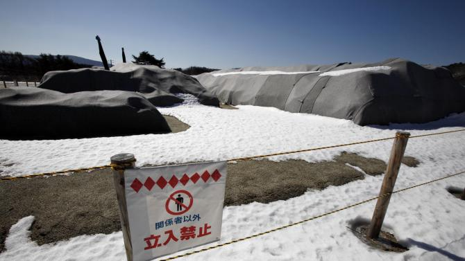 In this Monday, March 4, 2013 photo, a sign warns people to say out of an area where piles of radiation-contaminated soil sit on the sports field of a school in the abandoned town of Yamakiya,  outside the exclusion zone surrounding the Fukushima Dai-ichi nuclear plant in Japan. Two years after the triple calamities of earthquake, tsunami and nuclear disaster ravaged Japan's northeastern Pacific coast, radioactive and chemical contamination remains a threat as clean-up projects face troubles with organized crime and mishandling. (AP Photo/Greg Baker)