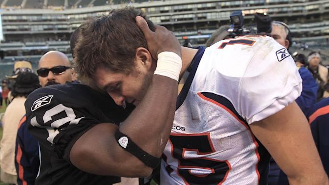 Denver Broncos quarterback Tim Tebow (15) hugs Oakland Raiders wide receiver Jacoby Ford (12) after an NFL football game in Oakland, Calif., Sunday, Nov. 6, 2011. (AP Photo/Marcio Jose Sanchez)