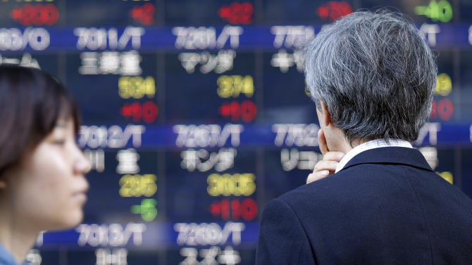 A man looks at an electronic stock board of a securities firm in Tokyo, Thursday, June 27, 2013. Stock markets from Sydney to Shanghai extended gains for a second day Thursday after the U.S. said quarterly growth may be weaker than expected, raising investors' hopes that the Federal Reserve would delay plans to wind down its stimulus program.(AP Photo/Koji Sasahara)