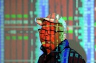 An investor walks past a screen as a projector's light reflects on his face at a local securities house in Taipei on December 1. Taiwanese authorities said Tuesday they will intervene in the island's stock market and spend up to $16 billion on shares, after it was hit hard by the fall-out from Europe's deepening debt crisis