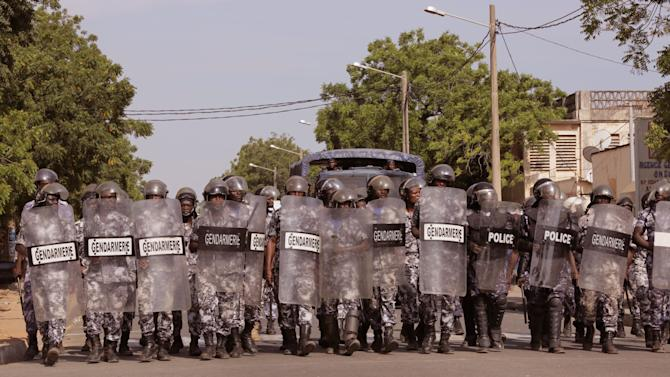 In this photo taken on Friday, Nov. 21, 2014, Togo troops in riot gear approach protestors in the capital city of Lome, Togo, during clashes with protesters calling for the president to withdraw from a presidential vote in March 2015. Security forces in Togo used rubber bullets and tear gas to disperse thousands of demonstrators calling for term limits that would bar President Faure Gnassingbe from running for a third term in office. (AP Photo/Erick Kaglan)