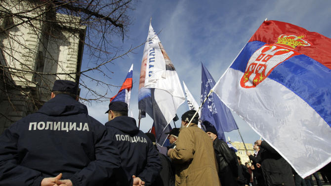 A protester waves a Serbian flag by police officers during the protest in front of the presidency building in Belgrade, Serbia, Tuesday, Feb. 5, 2013. Dozens of ultra-nationalists have accused Serbia's president of treason for agreeing to meet with his counterpart from Kosovo for the first time since the end of the war in 1999. The talks between Tomislav Nikolic and Atifete Jahjaga on Wednesday in Brussels, Belgium, will be part of an EU-brokered effort to improve ties between the former foes. (AP Photo/Darko Vojinovic)