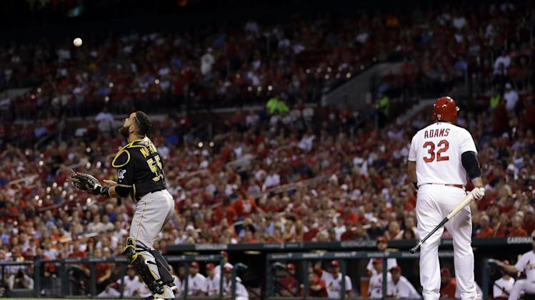 Pittsburgh Pirates catcher Russell Martin, left, catches a pop-up by St. Louis Cardinals' Matt Adams as Adams starts to walk back to the dugout during the first inning of a baseball game Tuesday, Sept. 2, 2014, in St. Louis. (AP Photo/Jeff Roberson)