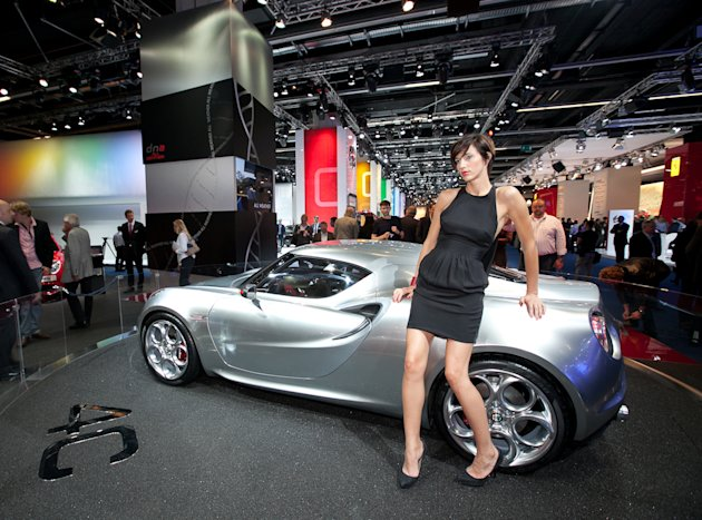 A hostess leans on the Alfa Romeo Concept Car 4C during the press day of the Frankfurt Auto Show IAA in Frankfurt, Germany, Tuesday, Sept. 13, 2011. The fair opens its doors to the public Sept. 15 to