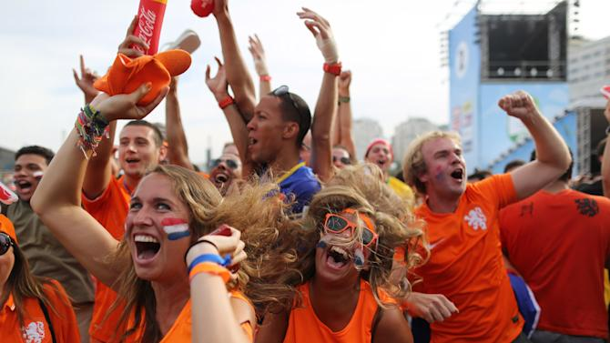 Soccer fans, decked out in orange, the Netherlands' national color, celebrate the second goal scored by Memphis Depay, while watching a live broadcast of the group B World Cup match between Chile and Netherlands, inside the FIFA Fan Fest area on Copacabana beach, in Rio de Janeiro, Brazil, Monday, June 23, 2014. Netherlands won 2-0, taking the top spot in group B. (AP Photo/Leo Correa)