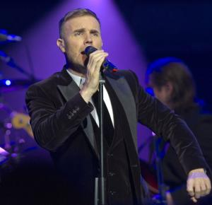 """FILE - This Dec. 6, 2011 file photo shows British singer-songwriter Gary Barlow performing during a fund-raising concert attended by Britain's Prince William and Catherine, Duchess of Cambridge, Prince Charles, Prince of Wales and his wife Camilla, Duchess of Cornwall, at the Royal Albert Hall in London. Barlow and his wife Dawn say their daughter was stillborn, and are asking for privacy """"at this painful time."""" In a statement released Monday, Aug. 6, 2012, the couple said they were devastated by the loss of Poppy Barlow, who was delivered stillborn on Saturday.  They said their focus is  """"on giving her a beautiful funeral and loving our three children with all our hearts."""" The couple have a son and two daughters. (AP Photo/Arthur Edwards, file)"""