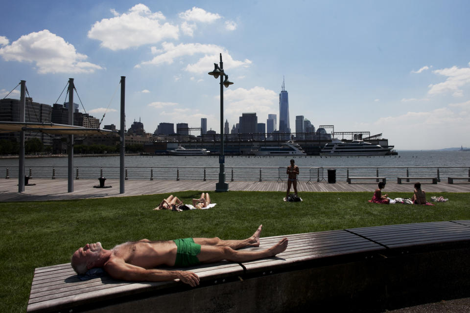 A man sunbathes in Hudson River Park during a heat wave, Tuesday, July 16, 2013 in New York. Forecasts are predicting temperatures in the 90s through Saturday. (AP Photo/Mark Lennihan)