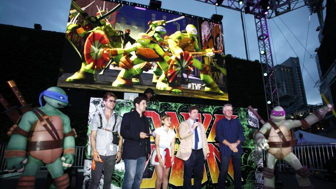 COMMERCIAL IMAGE - Cast members of 'Teenage Mutant Ninja Turtles' Greg Cipes, Jason Biggs, Mae Whitman, Sean Astin and Rob Paulsen pose for a photo with the teenage mutant ninja turtles at the Dawn Of The Con at Petco park during Comic-Con on Thursday, July 12, 2012, in San Diego, Calif. (Photo by Joe Kohen/Invision for Nickelodeon/AP Images)