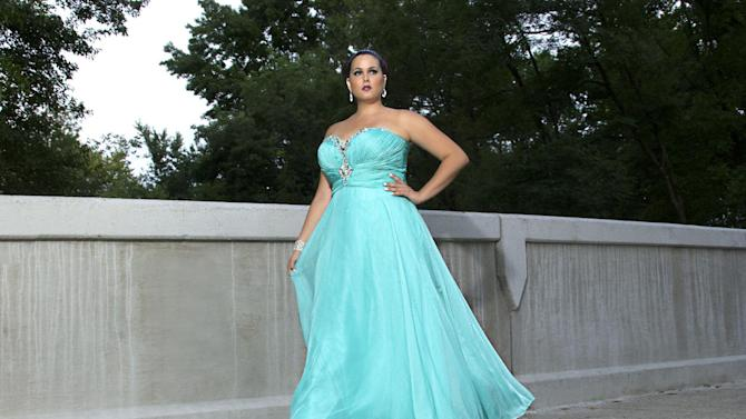 This product image released by Sydney's Closet shows a woman modeling a plus size prom dress. Clothes shopping for plus-size teens can be frustrating in general, but shopping for a dream prom dress can be a tear-inducing, hair-pulling morass of bad design and few options _ especially for girls who want a dress that hugs the body instead of tenting it. (AP Photo/Sydney's Closet)