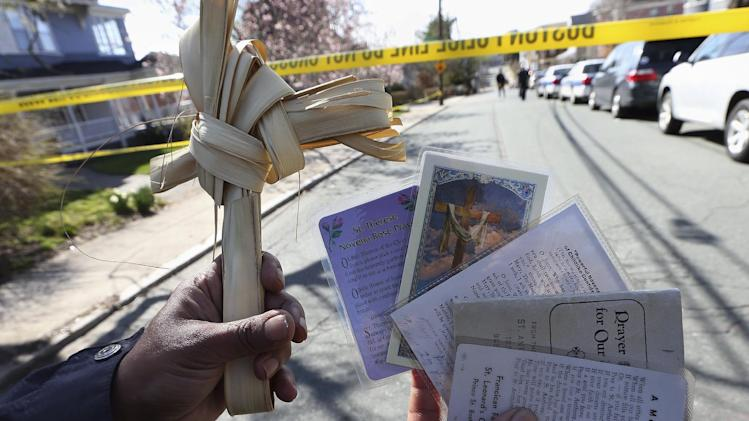 Ethel Rose Paris holds up some religious items she brought to leave at the house of Martin Richard beyond a police cordon in the Dorchester neighborhood of Boston, Wednesday, April 17, 2013.   Richard, 8, was killed in Monday's bombings at the finish line of the Boston Marathon. (AP Photo/Michael Dwyer)