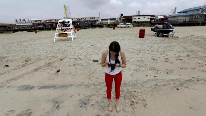 In this Friday, May 24, 2013 photo, Jasmine Wilker, 15, of Robbinsville, N.J., takes a photograph of writing she put on the sand on the beach, in Seaside Heights, N.J. The Jersey Shore beaches officially opened for the summer on Friday, after rebuilding following the destruction left behind by Superstorm Sandy last fall. The storm caused $37 billion of damage in the state. (AP Photo/Julio Cortez)