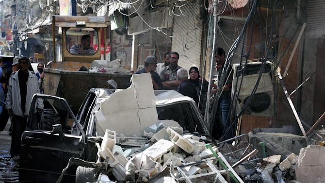 In this photo released by the Syrian official news agency SANA, Syrian citizens gather at the scene of a car bomb exploded in the residential al-Tadhamon neighborhood in Damascus, Syria, Tuesday, Sept. 24, 2013. Syrian state media say a car bomb has exploded in Damascus, killing and wounding a dozen people. Damascus has been hit by a wave of explosions over the past leaving scores of people dead. (AP Photo/SANA)