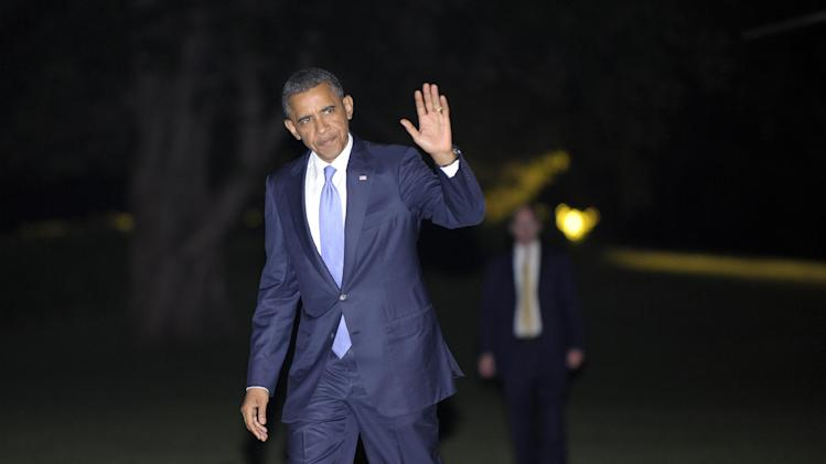 President Barack Obama waves as he walks from Marine One on the South Lawn to the White House in Washington, Monday, July 30, 2012. Obama spent the evening in New York City attending a fundraising event. (AP Photo/Susan Walsh)