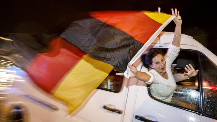 German fans celebrate as they drive along the 'Reeperbahn' red light district in Hamburg after Germany won the World Cup soccer final against Argentina