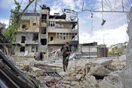 A Syrian rebel runs across a heavily damaged street to dodge sniper fire during clashes with government forces in the Saif al-Dawla district of the northern city of Aleppo