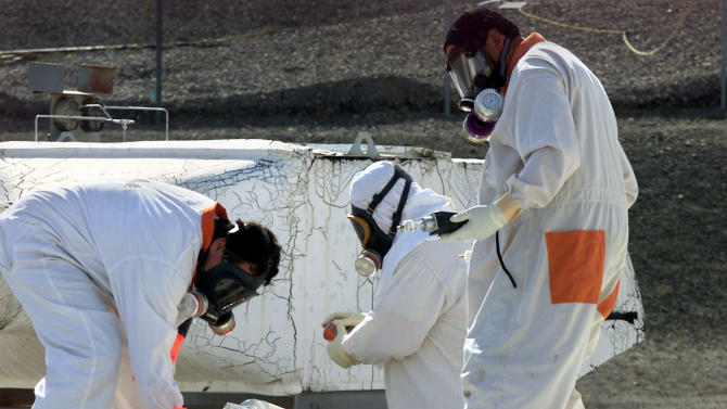 "FILE -- In this March 23, 2004 file photo, workers at the tank farms on the Hanford Nuclear Reservation near Richland, Wash., measure for radiation and the presence of toxic vapors. Six underground radioactive waste tanks at the nation's most contaminated nuclear site are leaking, Gov. Jay Inslee said Friday, Feb. 22, 2013. Inslee made the announcement after meeting with federal officials in Washington, D.C. Last week it was revealed that one of the 177 tanks at south-central Washington's Hanford Nuclear Reservation was leaking liquids. Inslee called the latest news ""disturbing."" (AP Photo/Jackie Johnston, File)"