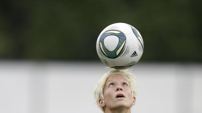"""FILE - In this Thursday, July 14, 2011 file photo, United States' Megan Rapinoe bounces a ball with her head during a training session in preparation for the final match against Japan during the Women's Soccer World Cup in Frankfurt, Germany. Rapinoe, a midfielder on the American soccer team at the 2012 Olympics, prepares for competition with a pre-game ritual. """"I put my headphones on the bus from when we leave the hotel over to the stadium, just kind of getting into the zone, just kind of relax and get into it."""" (AP Photo/Marcio Jose Sanchez)"""